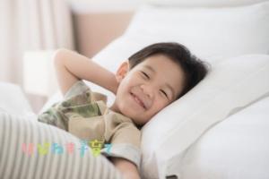 ベッドで微笑む男の子